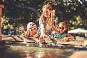 Mother and her daughters playing in the city square fountain.They sprayed with water.Refreshing on hot summer day.