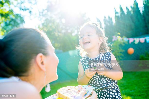 Mother and her little daughter having fun in the garden