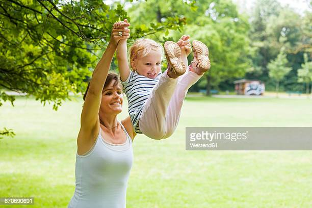 Mother and her little daughter playing together in a park