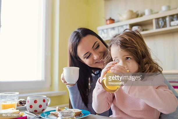 Mother and her little daughter together at breakfast table