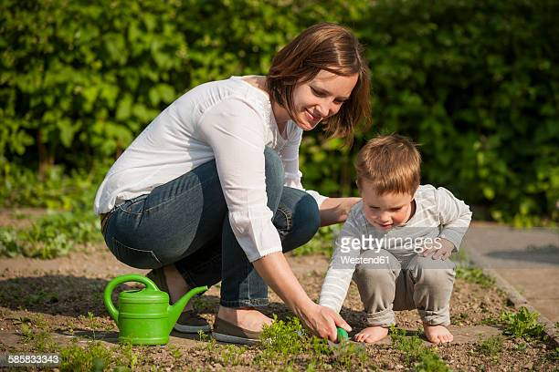 Mother and her little son gardening