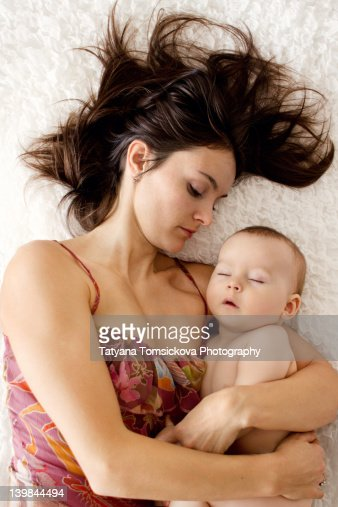 Mother and her son lying on bed : Stock Photo