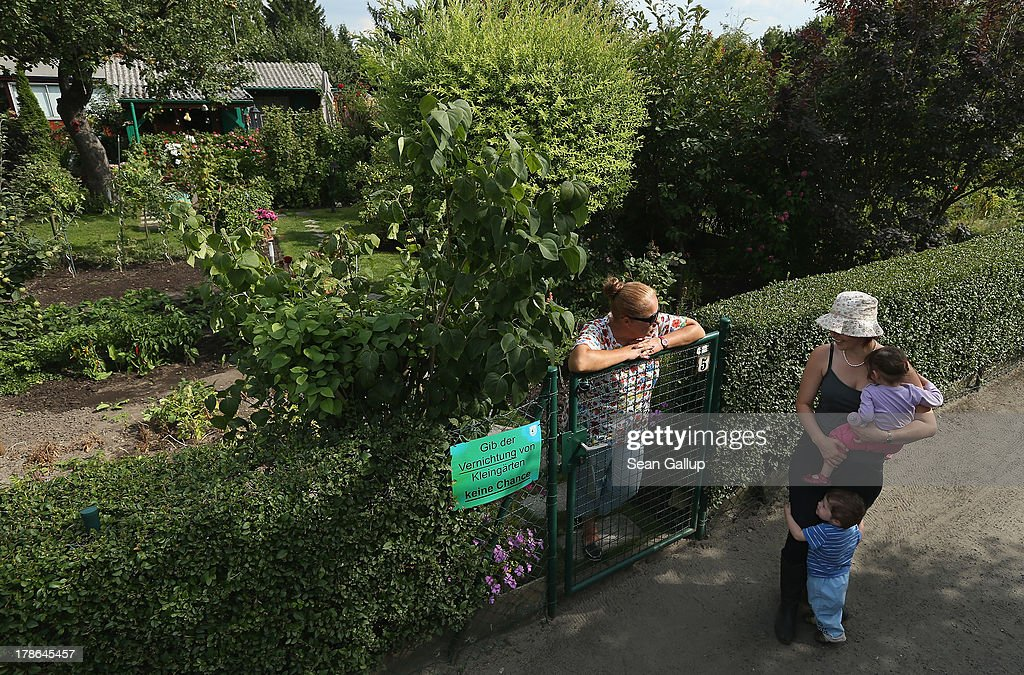 A mother and her two children chat with a member at the Oeynhausen Small Garden Association garden colony on August 29, 2013 in Berlin, Germany. At the Oeynhausen colony about 300 of its 438 gardens are currently threatened by real estate development, as are about another 24 colonies across the city. Berlin has about 900 garden colonies that are owned by the city and that provide urban dwellers who don't have land of their own the opportunity to maintain a garden and escape the stress of urban life. Berlin is currently undergoing a housing squeeze and city authorities are beginning to sell some of the colonies to developers, which has caused outrage in a city where the colonies of small gardens are a deep-seated tradition going back over a century.