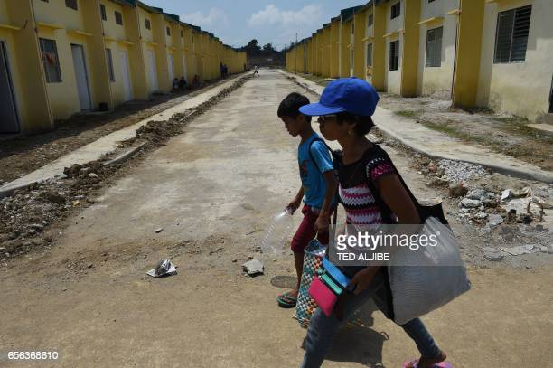 A mother and her young son carrying their belongings walk past row of houses originally built by the government for uniformed personnel and which has...