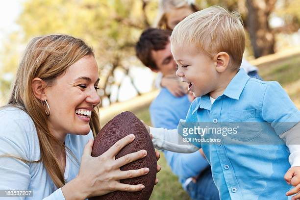 Mother and Her Young Son Playing With Football at Park