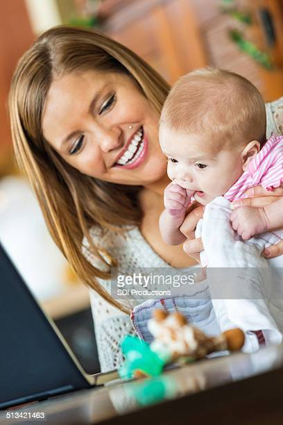 Mother and infant daughter video chatting with laptop at home