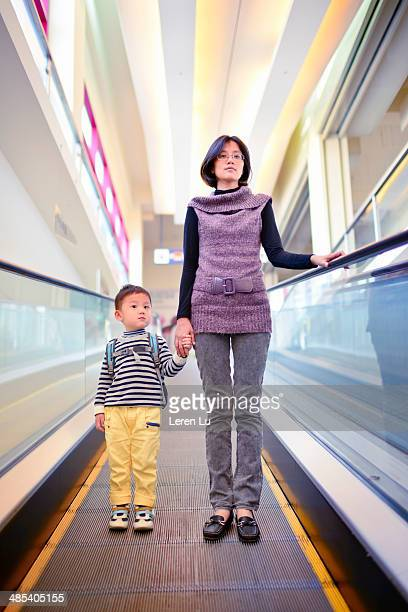Mother and kid standing on escalator.