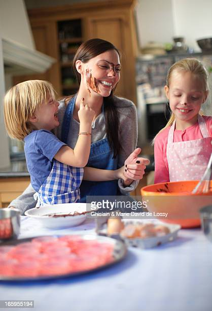 Mother and kids baking a cake, messy