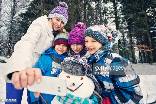 Mother and kids building a snowman on winter day
