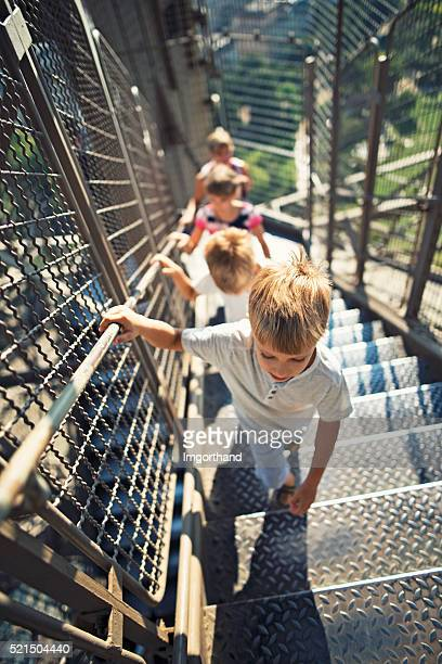 Mother and kids climbing stairs of Eiffel Tower