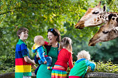Mother and children, school student, little toddler boy, preschool girl and baby watching and feeding giraffe animals at the zoo. Wildlife experience for parents and kids at animal safari park.
