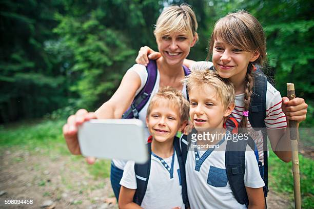 Mother and kids hikers taking selfie in forest