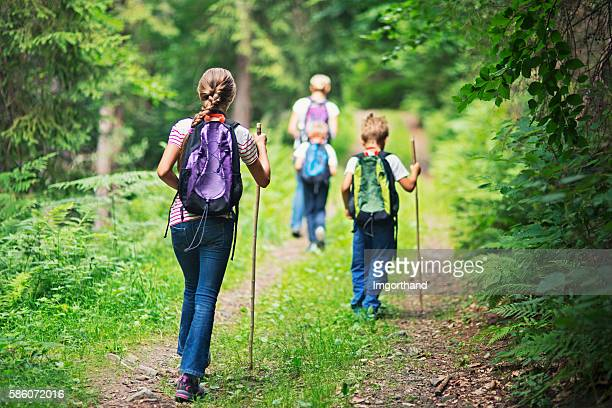Mother and kids hiking in forest