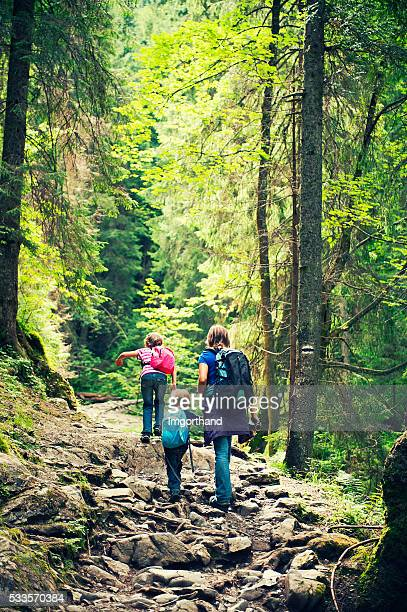 Mother and kids hiking on difficult stone path