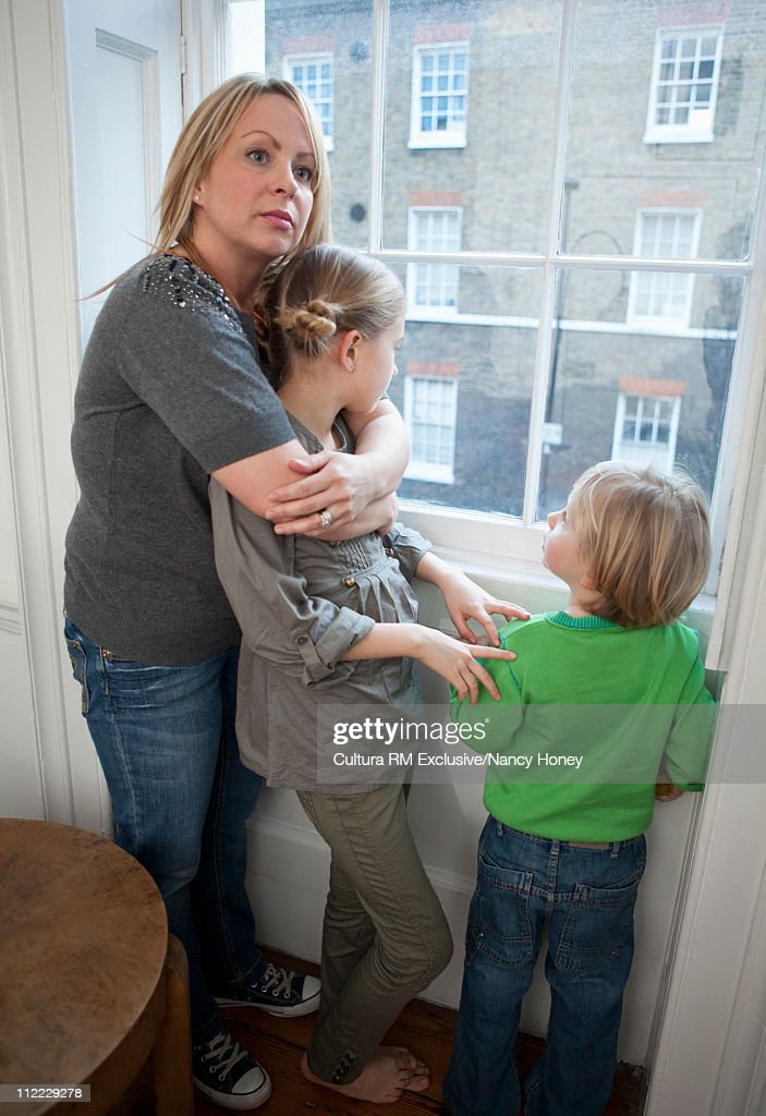 Mother and kids hugging in window : Stock Photo