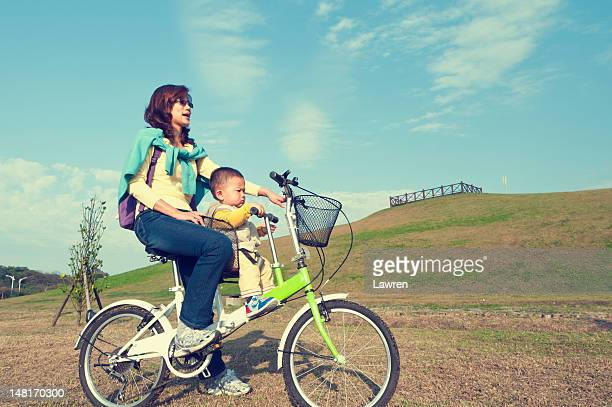 Mother and little boy driving bicycle