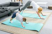 Mother and little boy in adho mukha svanasana position on yoga mats