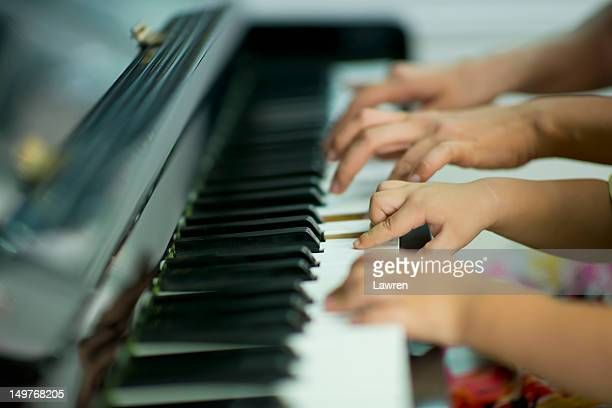 Mother and little boy playing piano
