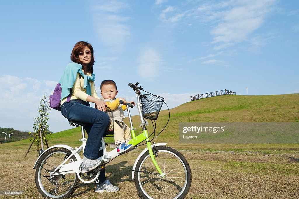 Mother and little boy riding bicycle : Stock Photo