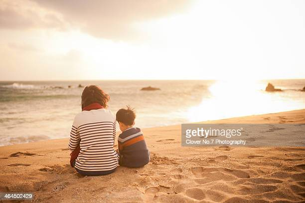 Mother and little boy sitting on the beach