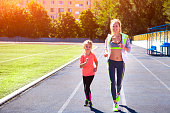 Mother and little daughter are doing exercise in the stadium. Family doing fitness at the stadium. Healthy family concept