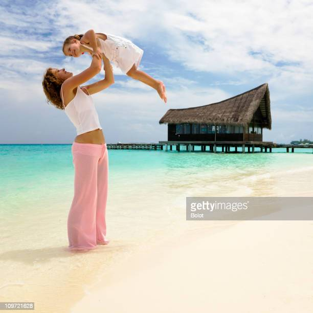 Mother and little daughter playing by tropical beach hut