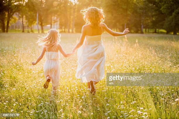 Mother and little daughter running across a golden meadow