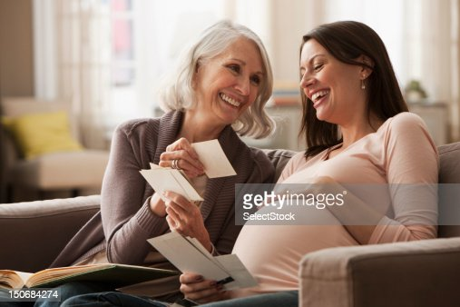 Mother and pregnant daughter sharing photographs : Stock Photo