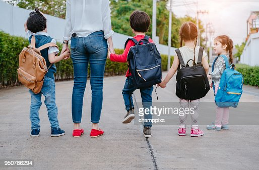 Mother and pupil and kids holding hands going to school in first class with schoolbag or satchel walking to school bus, Parent and son,sister preschool : Foto stock