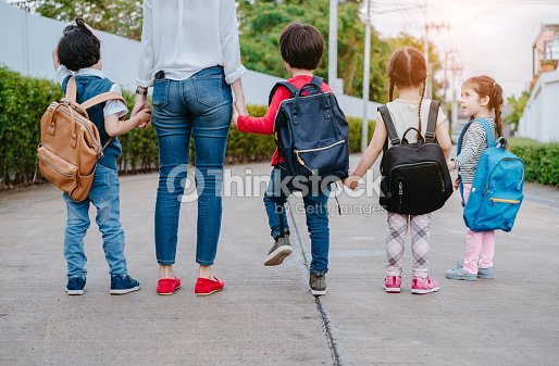 Mother and pupil and kids holding hands going to school in first class with schoolbag or satchel walking to school bus, Parent and son,sister preschool : Stock Photo