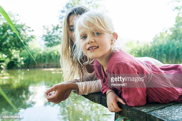 Mother and smiling daughter lying on jetty at a lake