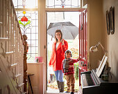 Mother and son arriving at front door of home on rainy day, portrait