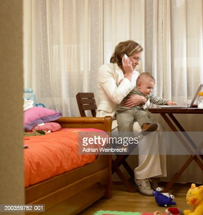 mother and son at desk in bedroom woman using telephone