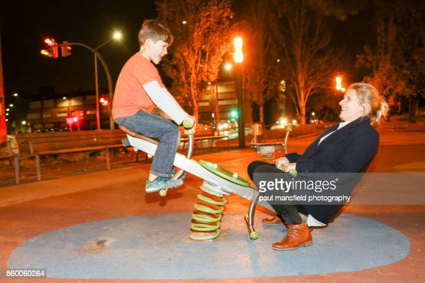 Mother and son at playground after dark