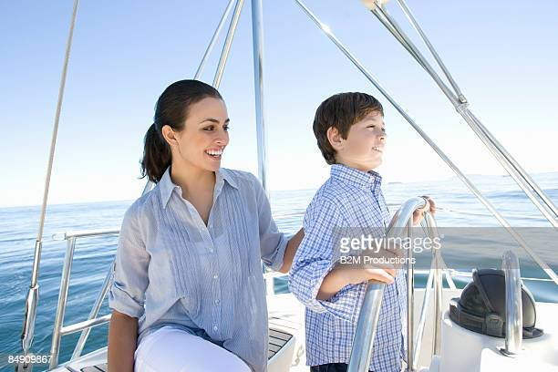 Mother and son (6-8) at wheel of sailboat