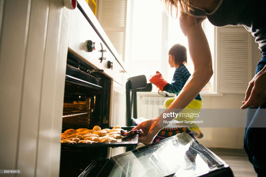 Mother and son baking cookies in kitchen