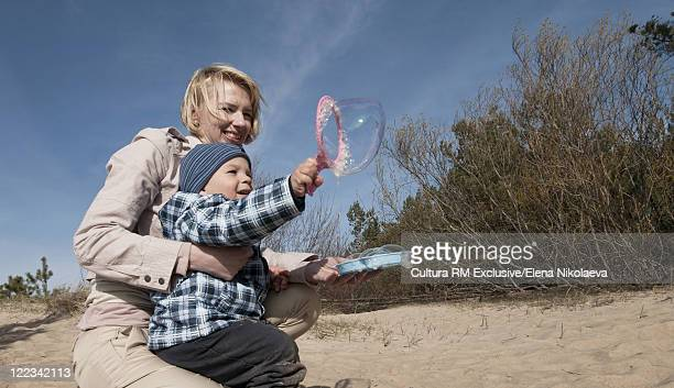 Mother and son blowing bubbles at beach