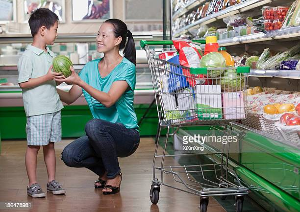 Mother and son buying watermelon in supermarket, Beijing