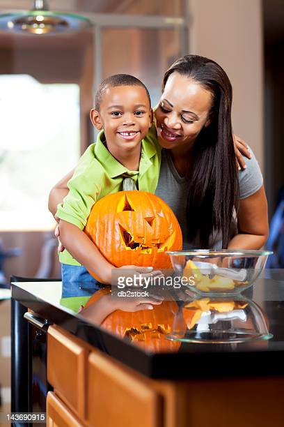 Mother and son carving jack-o-lantern