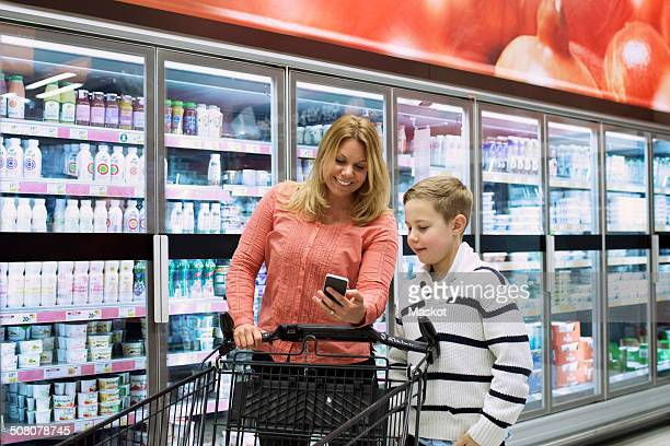 Mother and son checking shopping list on mobile phone in grocery store
