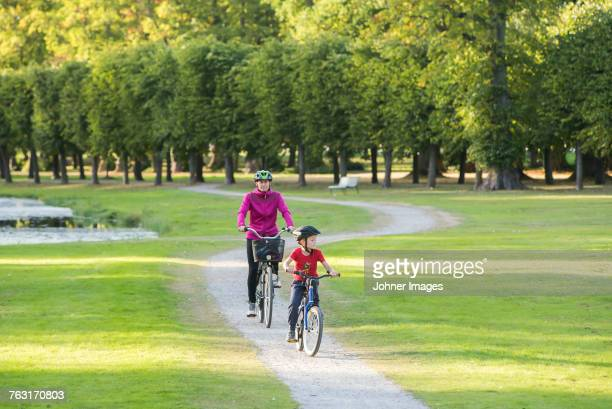 Mother and son cycling in park