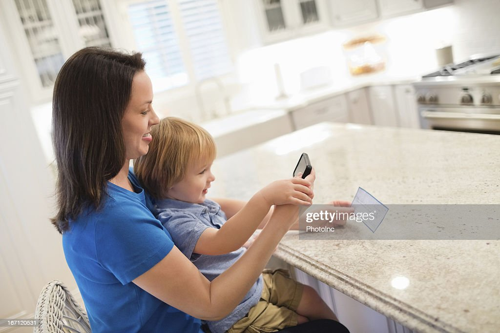 Mother And Son Depositing Check Through Smart Phone