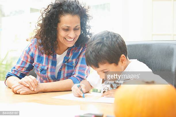 Mother and son drawing at dining table