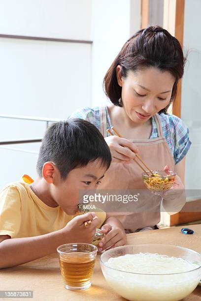 Mother and son eating noodle together