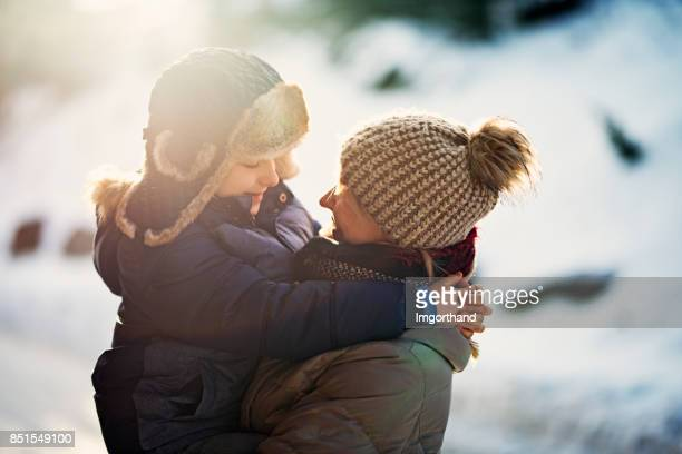 Mother and son embracing on a sunny winter morning