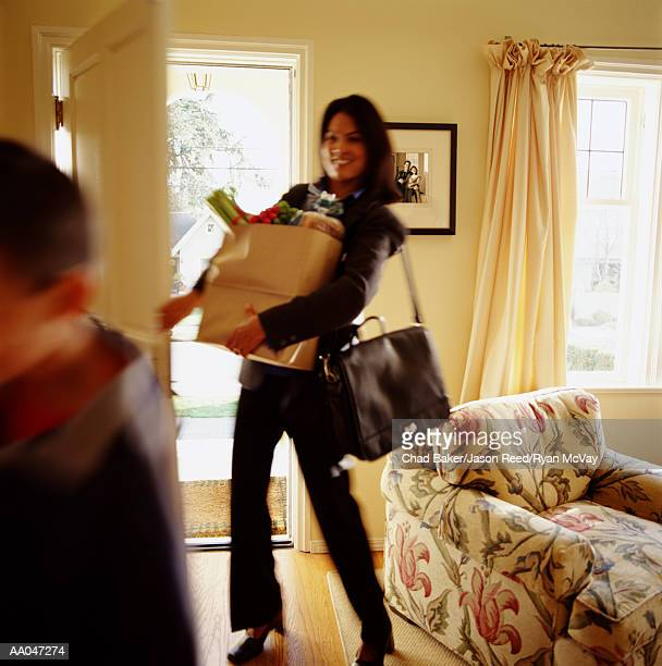 Mother and son (8-10) entering home, woman carrying groceries