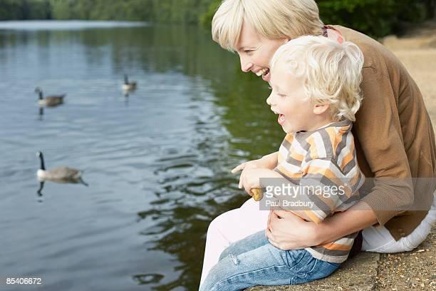 Mère et son fils de nourrir les canards dans l'étang