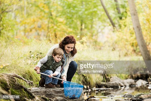 Mother and son (4-5) fishing in mountain stream : Stockfoto