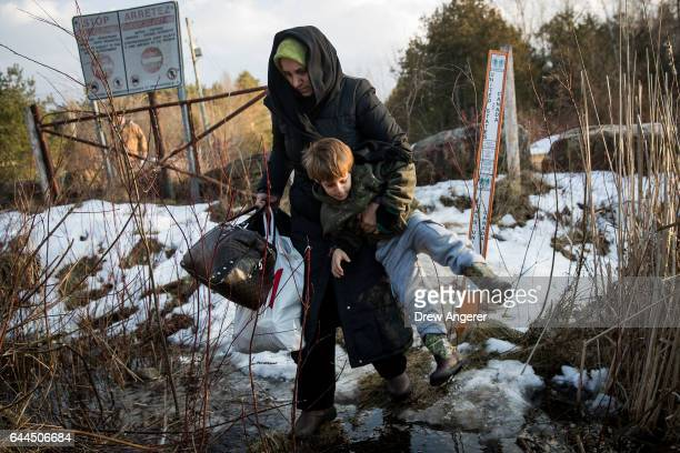 A mother and son from Turkey walk through a creek as they cross the USCanada border into Canada February 23 2017 in Hemmingford Quebec In the past...