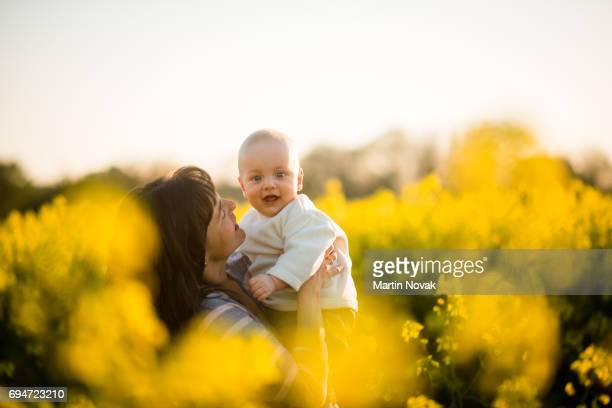 Mother and son. Happy family together at rapeseed field.